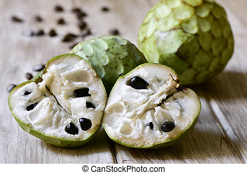 custard apples on a wooden surface - closeup of some custard...