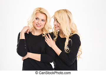 Attractive cheerful young blonde sisters twins talking and...