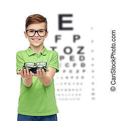 happy boy holding eyeglasses over eye chart - childhood,...