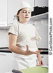 Boy throwing dough up - Caucasian boy throwing up dough...
