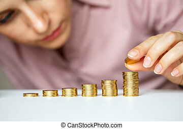 Female hand stacking gold coins into increasing columns -...