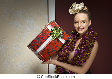 woman with tinsel and christmas git - happy smiling female...