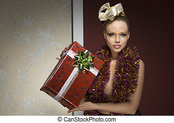 woman with tinsel and christmas git - sensual girl with...