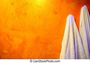towels hanging on an orange wall