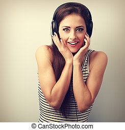 Surprising happy woman in headphones listening the music....