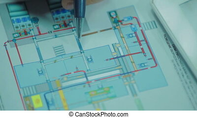 Man is checking drawing of mechanical equipment. Close up