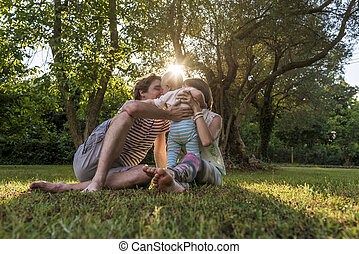 Young family sitting in a grass in park