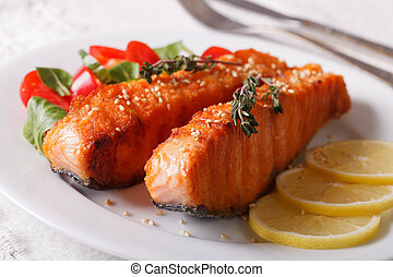 Grilled salmon fillet with sesame and lemon closeup on a plate. horizontal