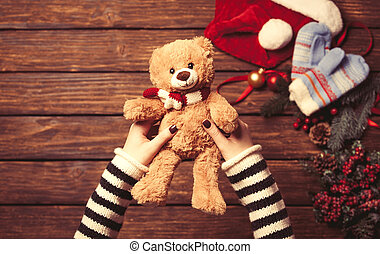 Female holding a little teddy bear near christmas gifts...