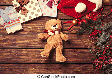 Teddy bear and christmas toys on wooden background