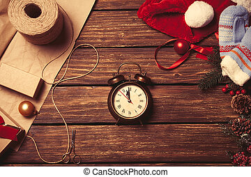 Alarm clock and christmas gifts on wooden background