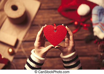 Woman holding a heart shape toy in the hands before wrapping...