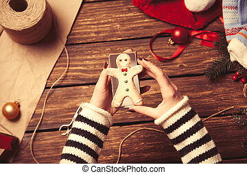 Woman wrapping a christmas cookie on wooden background,...