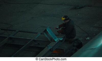 Worker welding in a factory