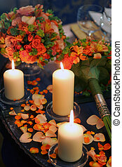 Burning candles flowers and petals - Burning candles on...