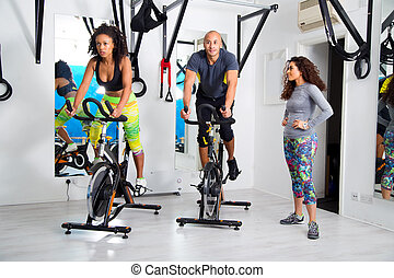 group at the gym - group exercising at the gym on spinning...