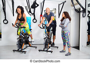 group at the gym - group exercising on bikes in a fitness...