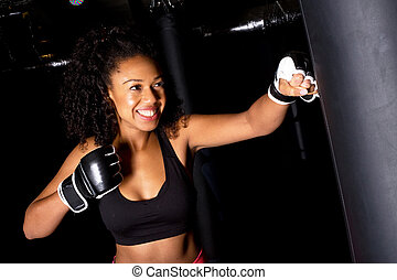 girl boxing - young woman punching a punch bag