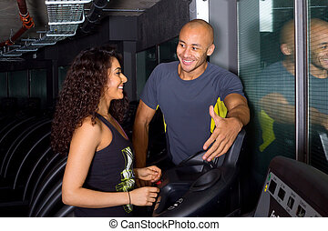 training at the gym - personal trainer training a young...