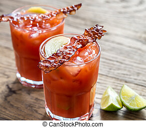 Two glasses of Bloody Mary with bacon rashers