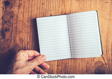 Man flipping pages of blank notebook - Top view of male hand...