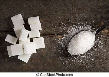 White sugar in silver spoon on wood table