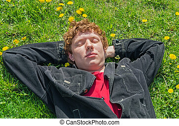 Lying on grass - Young guy lying on the field with...