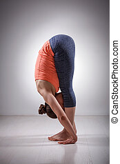 Sporty fit woman practices yoga asana Uttanasana - Sporty...