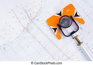 orange theodolite prism lies on a background geodetic maps...