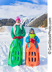 Happy kids sledding - Happy cute girl with her brother...