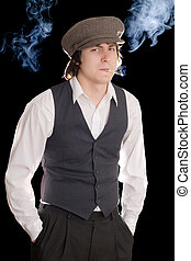 Young man smoking with guarded look Isolated on black