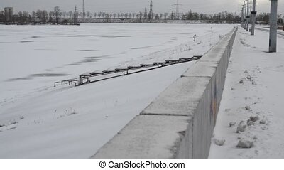 Man in white clothes climbing a dike of frozen water storage...