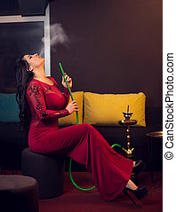 Woman smoking hookah in bar - Young attractive girl in...
