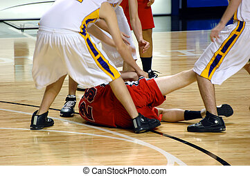 Down for the Count - Boys player on basketball team hangs on...