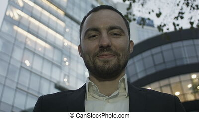 Portrait of young business man on office building background. Caucasian man with beard smiling.