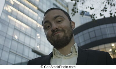 Portrait of young business man with beard smiling show tumb up, on office building background. Caucasian man.