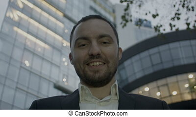 Two thumbs up, portrait of young business man on office building background. Caucasian man with beard smiling.