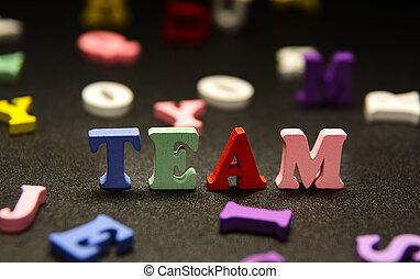 Team   multicolored letters   on black