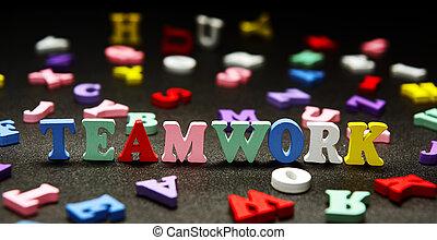 Teamwork   multicolored letters   on black