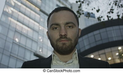 Severe look of bearded business man, office building at the...