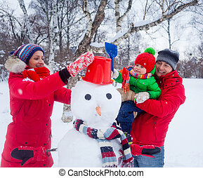Family with a snowman - Happy family of three making a...