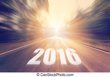 Abstract blurred country road and field and with,sunlight. Forward target to the New Year 2016.