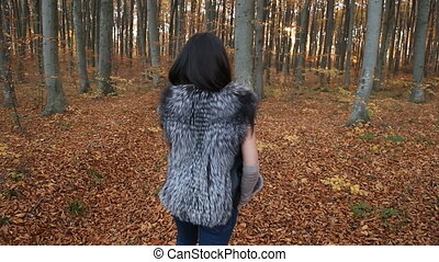 woman walking in nature - girl walking in the autumn forest