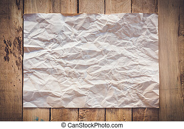 old paper crumpled on wood background with space