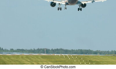 Airplane landing on take-off runway - Back view of a...