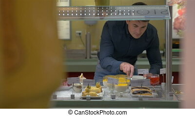 Man Choosing Bakery in Self-Service Buffet - Young man is...