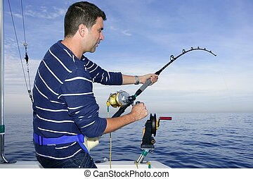 Angler fisherman fighting big fish rod and reel saltwater...