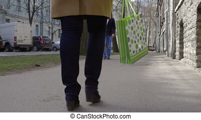 Woman walking in the city and carrying shopping bag - Slow...