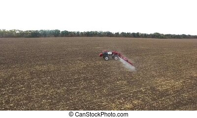 red tractor plowing the field corn. aerial shot - Tractor...