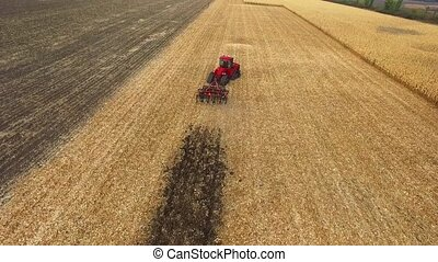 red tractor preparing land for sowing aerial shot, field...